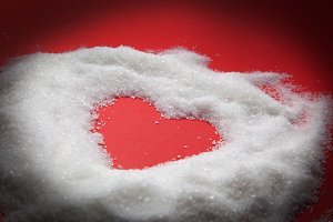 Heart of sugar on red background