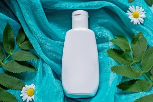 White bottle with cosmetic on green