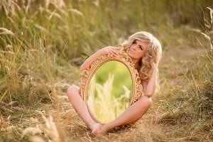 Blonde naked woman holds a mirror
