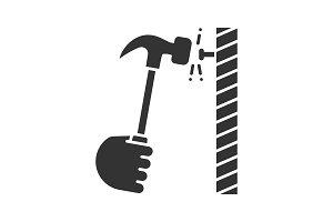 Hand hammering nail glyph icon