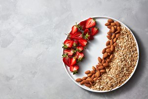 Plate with raw oatmeal, nut and