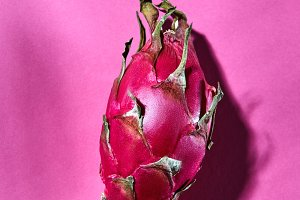 Juicy pink pitaya on a dark pink