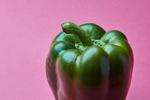 Fresh green paprika isolated on pink