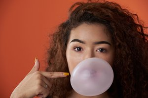 Headshot of woman with bubble gum ba