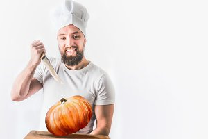 Chef holds whole pumpkin and knife