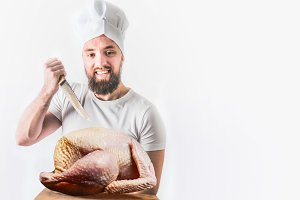 Chef with raw whole turkey and knife