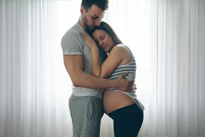 Pregnant woman embraced by her husba