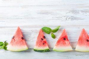 Watermelon pieces on white wooden ba