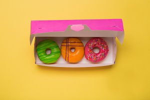 Color donuts in box on yellow