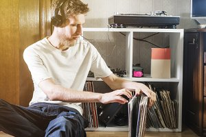 young man choose vinyl record to pla