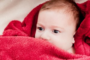 Baby boy covered with red blanket