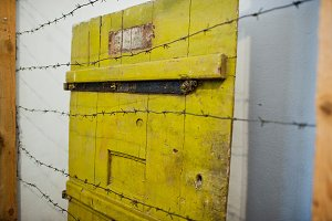 Yellow prison doors behind the barbe