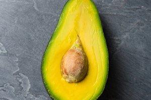 Half avocado on dark background