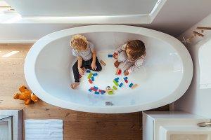 Siblings playing inside a bathtub