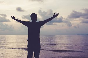 Man with open arms raised in the sky