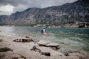 man kayaking in mountain bay
