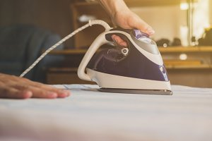 close up maid ironing clothes in hot