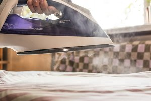 close up domestic iron with steam go