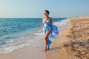 girl on the beach in a dress near th
