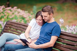 Couple using tablet and cellphone in