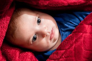Baby lying covered with red blanket