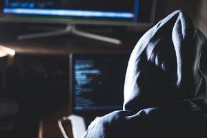 hacker in hoodie typing code in prog
