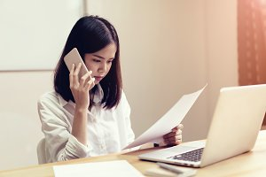 Businesswomen are using the phone to