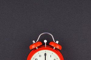 Red vintage alarm clock on dark back