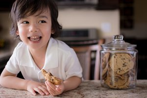 Happy Child Snacking on Cookie