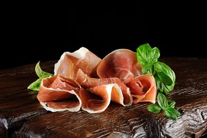 parma ham (jamon) sliced on a wooden