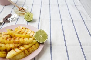 Grilled pineapple slices on a pink