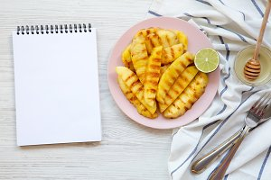 Grilled pineapple wedges on a pink