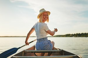 Smiling woman canoeing on a still la
