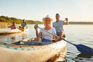 Smiling woman canoeing with friends