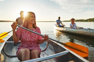 Smiling couple canoeing with friends
