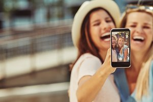 Laughing friends taking selfies toge