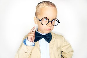 Little boy wearing glasses and a bow