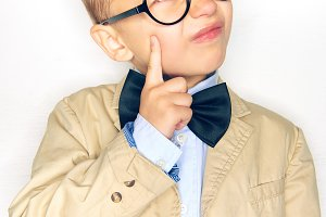 Little boy wearing a bowtie and glas