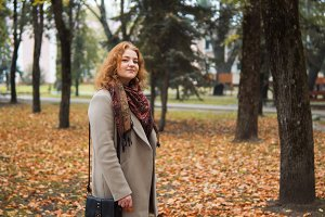 Young woman in coat walking in autum