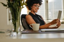 Happy woman using digital tablet by  in Business