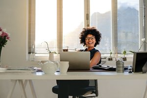 Businesswoman laughing at her desk