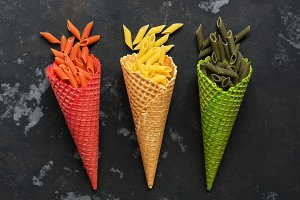Colored pasta in waffle cones on a