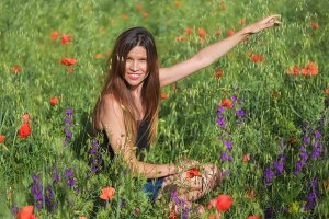 Woman enjoying a walk in poppy field