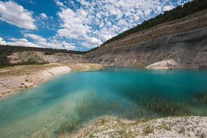 Turqoise lake in an open pit mine