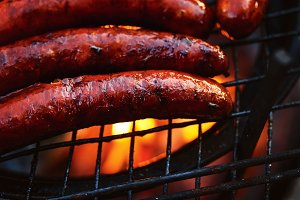 Grilled sausages on grill flames BBQ