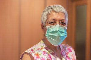Elderly woman wearing face mask.