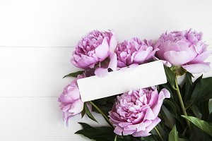 invitation card and pink peony flowe