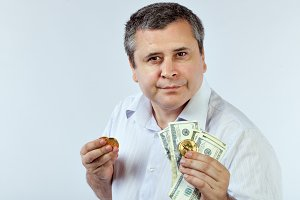 Man holds coins bitcoins and dollars