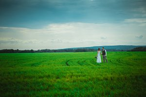 bride and groom stand on the backgro