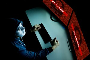 Hacker in mask under hood hacking an